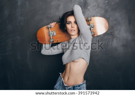 Funky girl posing with skateboard. Lifestyle portrait - stock photo