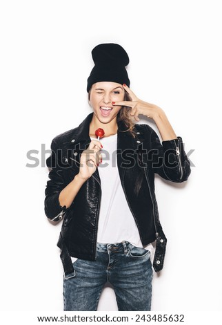 Funky hipster girl  saluting, winking and  sucking lollipop. White background, not isolated - stock photo