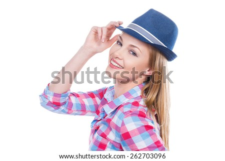 Funky style. Beautiful young woman in funky wear adjusting her hat and looking at camera while standing against white background - stock photo