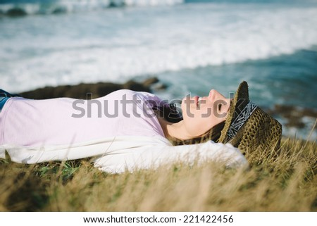 Funky young woman resting and relaxing towards the sea. Cheerful brunette enjoying silence and tranquility. - stock photo