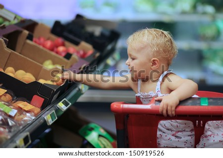 Funny adorable small baby girl in beautiful dress sitting in red shopping cart in supermarket at fruits and vegetables department, she is bending over trolley to pick up apricot from a box on shelf - stock photo