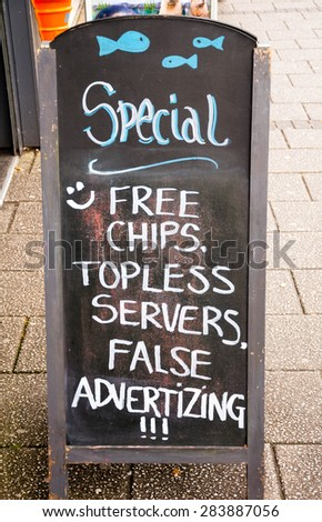 funny advertising board in front of a pub - stock photo