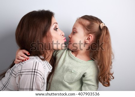 Funny amusing young mother wanting to kiss her comical grimacing daughter in studio - stock photo