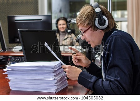 Funny anchorman in front of a microphone on the radio - stock photo