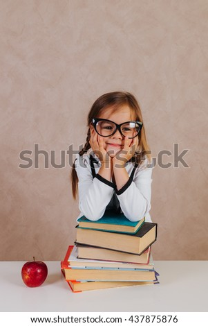 Funny and beautiful little cute schoolgirl in the classroom with books at the desk with emotions - stock photo