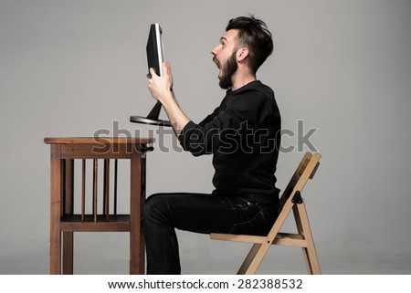Funny and crazy man using a computer on gray background. man's hands holding a monitor. Concept of surprise and indignation - stock photo