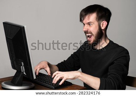 Funny and crazy man using a computer on gray background. man's hands on the keyboard - stock photo