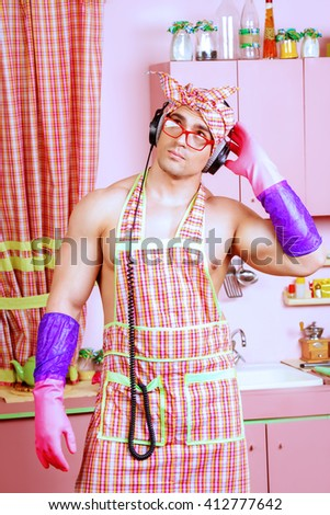 Funny and handsome muscular man in an apron takes a break from household chores, listening to music on headphones. Valentine's day. Women's day. - stock photo
