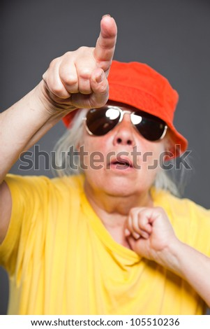 Funny and happy senior woman wearing yellow shirt and orange hat and sunglasses. Cool and hip. Studio shot isolated on grey. - stock photo