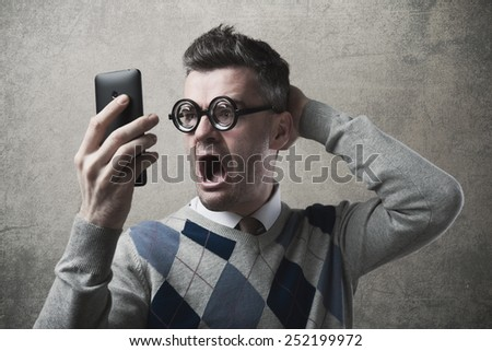 Funny astonished angry guy having troubles with his smartphone - stock photo