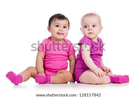 Funny babies girls sitting beside on floor - stock photo