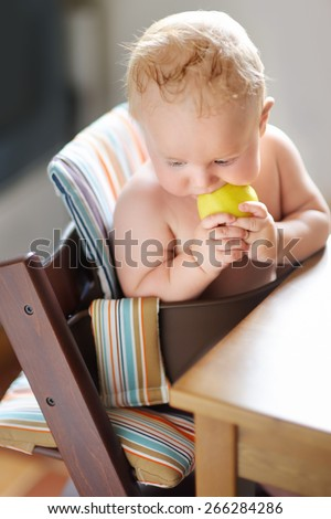 Funny baby boy eating healthy food (apple)  - stock photo