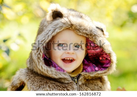 funny baby boy outdoors wearing fur costume - stock photo