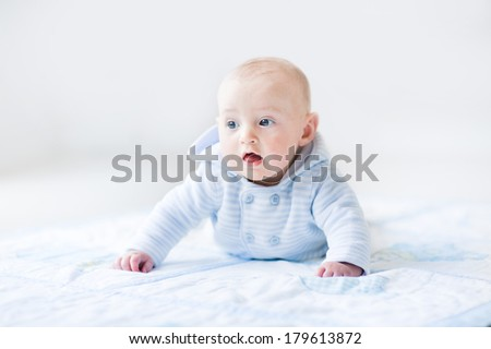 Funny baby boy playing on a blue blanket wearing a blue knitted sweater during tummy time in a sunny white room - stock photo