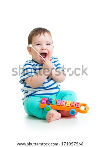 funny baby boy playing with musical toys