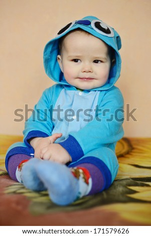 funny baby boy sitting on the sofa - stock photo