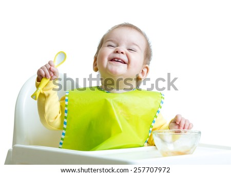funny baby child sitting in chair with a spoon