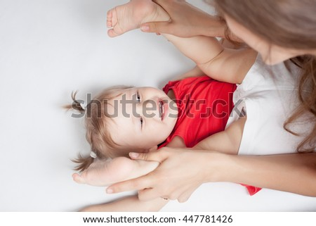Funny baby girl doing exercise and yoga with her happy mother on a white bed. Newborn looking at the camera and smiling. Mothercare is most important in baby life
