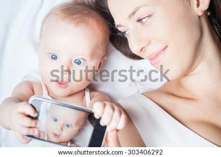 Funny baby girl make selfie on mobile phone and lying near her mother on a white bed. Newborn looking at the camera and smiling. Mothercare is most important in baby life - stock photo