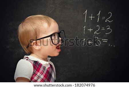 Funny baby girl pupil solves arithmetic examples on blackboard - stock photo
