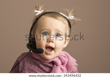 Funny baby girl talking on telephone headphones
