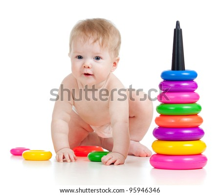 funny baby goes down on all fours with color toys - stock photo