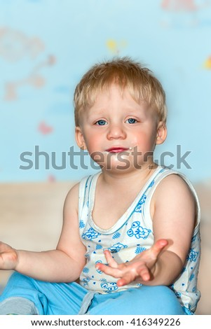 Funny baby grimaces. The baby's face smeared with ice cream. - stock photo