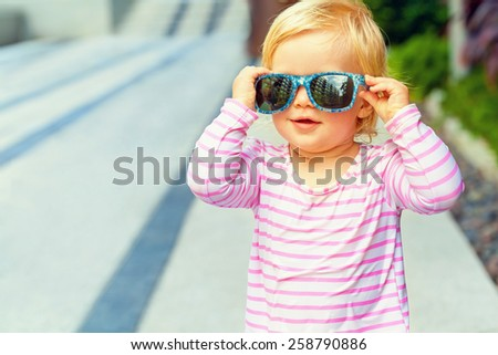 Funny baby in a swimsuit and sunglasses - stock photo