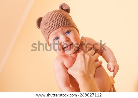 Funny baby in bear hat flying on the mother's hand - stock photo