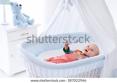 Funny baby in white crib with canopy. Nursery interior and bedding for kids. Laughing little boy playing in moses basket. Bedroom with bassinet for young children. Happy child in colorful pajamas. - stock photo