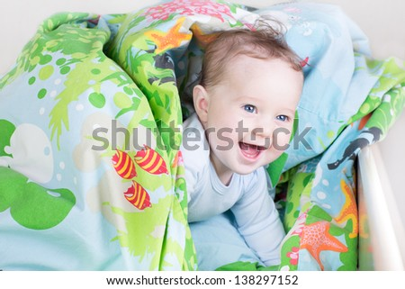 Funny baby playing in a bed under a blue blanket - stock photo