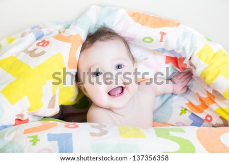 Funny baby playing peek-a-boo under a colorful blanket