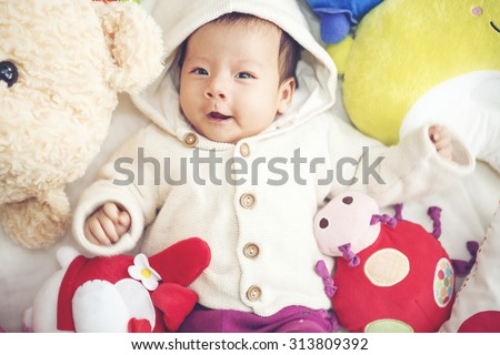 Funny Baby  playing with a beautiful doll - Vibrant color effect - stock photo