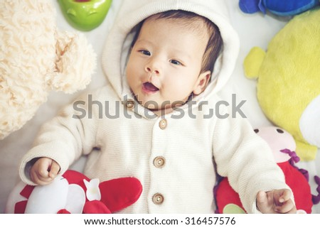 Funny Baby  playing with a beautiful doll - Vibrant color effect