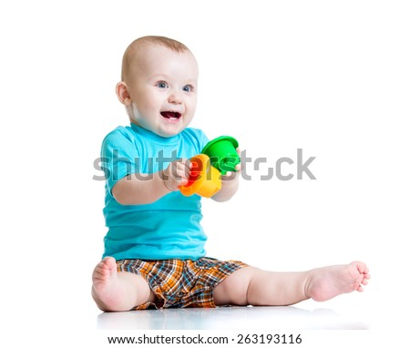 funny baby playing with colourful cup toys on floor, isolated over white