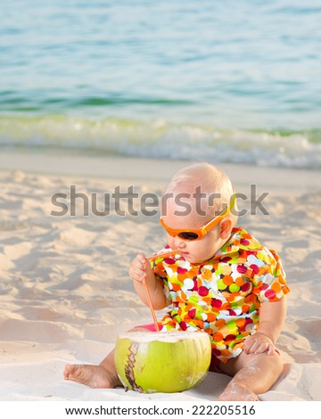 Funny baby with coconut on the beach
