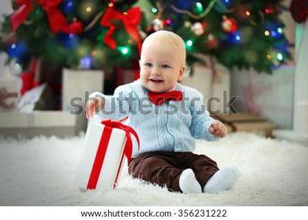 Funny baby with gift box and Christmas tree on background - stock photo