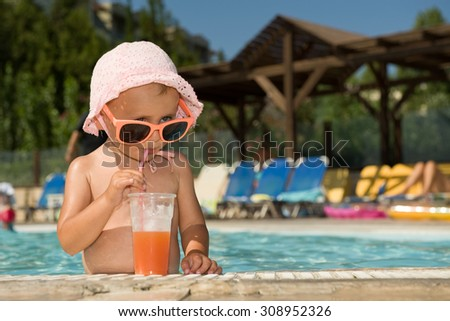 Funny baby with sunglasses and cocktail in outdoor swimming pool
