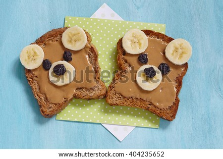 Funny bear face sandwich with peanut butter, banana and raisins - stock photo