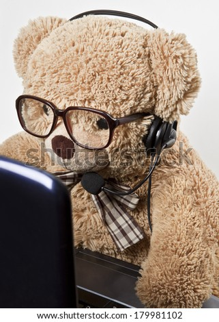 Funny bear in glasses and headphones at work behind the computer - stock photo