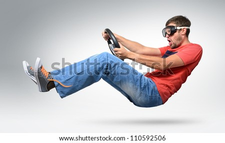 Funny bearded man car driver in goggles with a wheel, auto concept