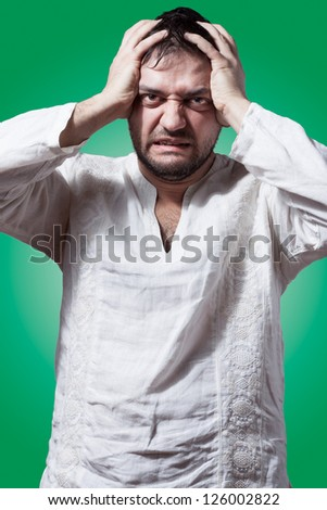 Funny bearded man with desperate expression on green background - stock photo