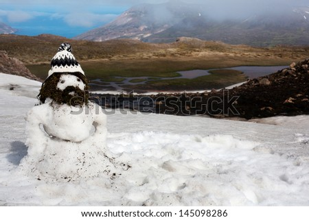funny bearded snowman in the traditional Icelandic knitted cap on a background of mountain scenery, Iceland - stock photo