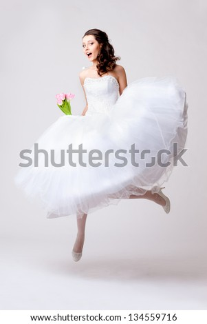 funny beautiful bride jumping in studio over white background