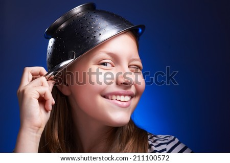 Funny beautiful teen girl with a colander on her head winking and smiling - stock photo