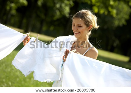 Funny beautiful woman hanging clothes on the line outdoors - stock photo