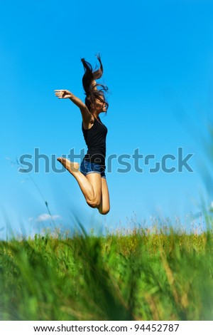 funny, beautiful, young woman jumps up on the background of green grass and blue sky
