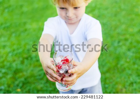 Funny blond toddler boy in summer garden playing with glass of berry ice cubes, creative summer activity with kids. Selective focus on hands - stock photo