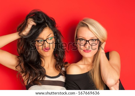 Funny blonde and brunette women portrait against red background.  - stock photo