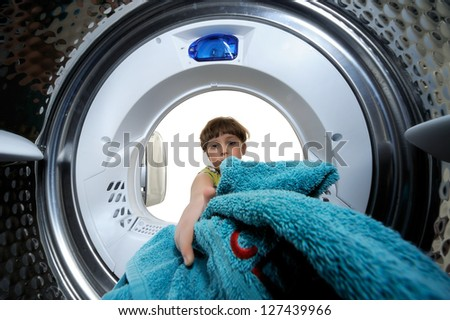 Funny boy loading clothes to washing machine. View from the inside of washing machine. - stock photo